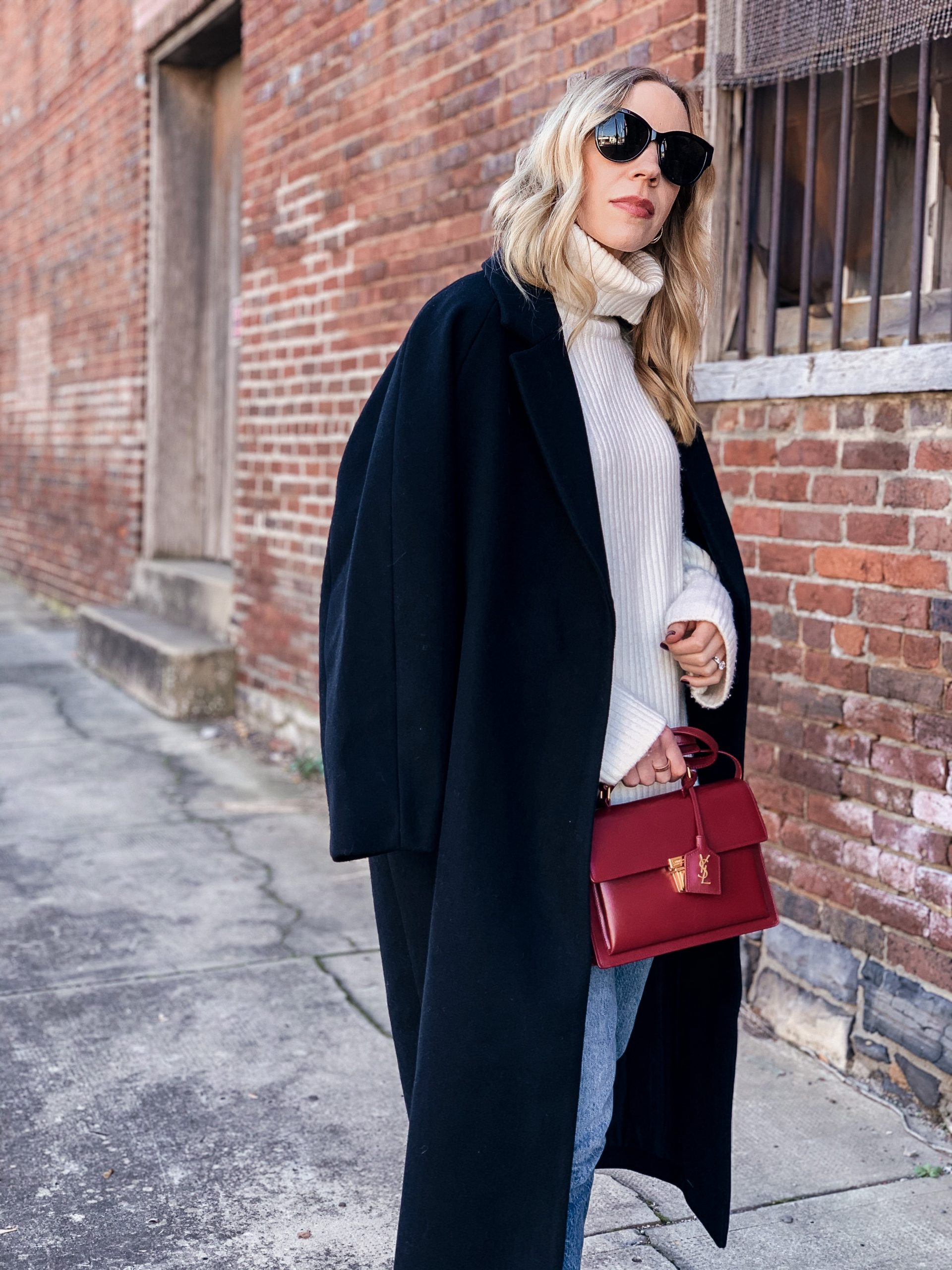 Meagan Brandon fashion blogger of Meagan's Moda wears oversized black wool coat over chunky cream sweater with red YSL bag