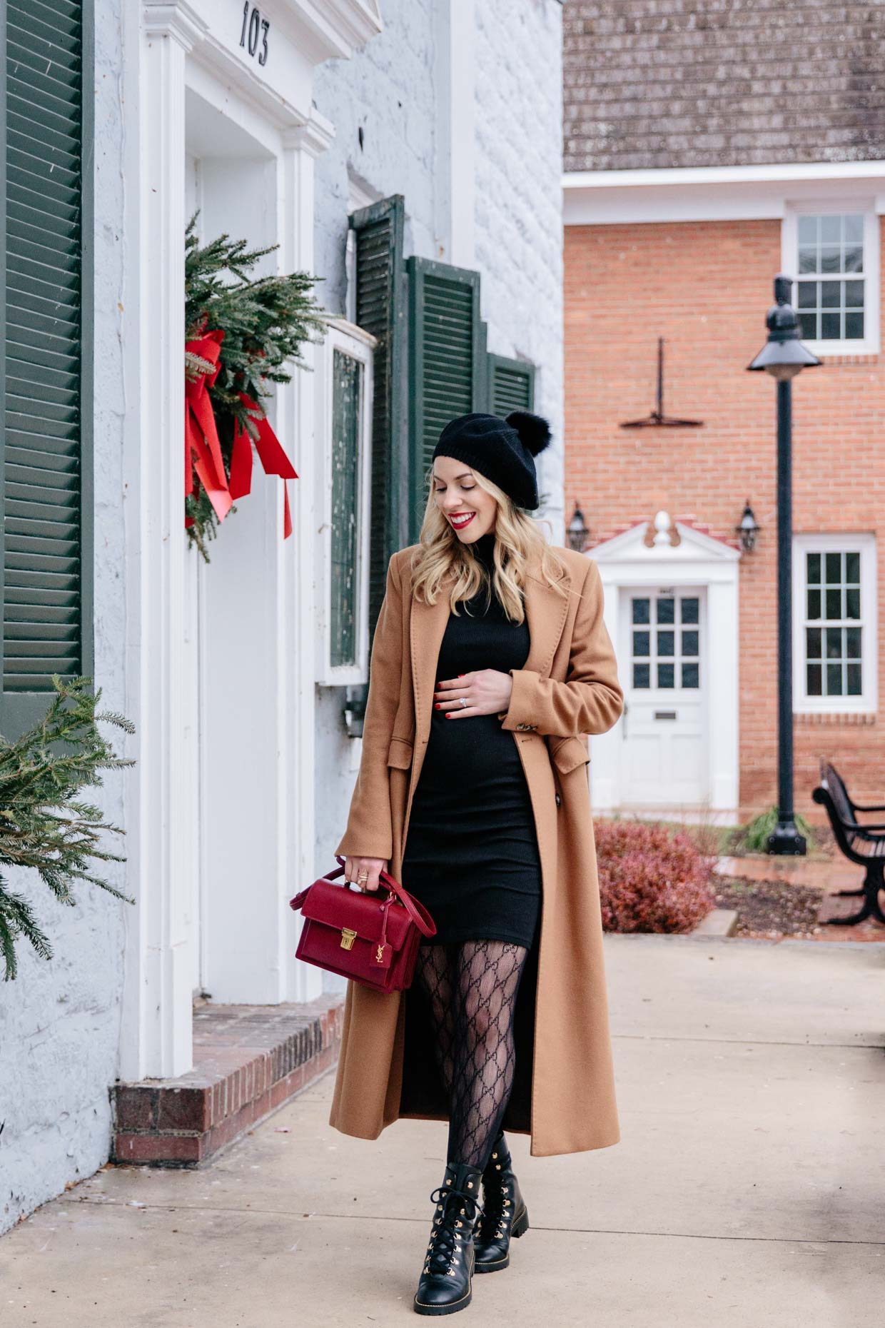 Meagan Brandon fashion blogger of Meagan's Moda wears double breasted camel coat over fitted black turtleneck dress with Gucci tights and combat boots
