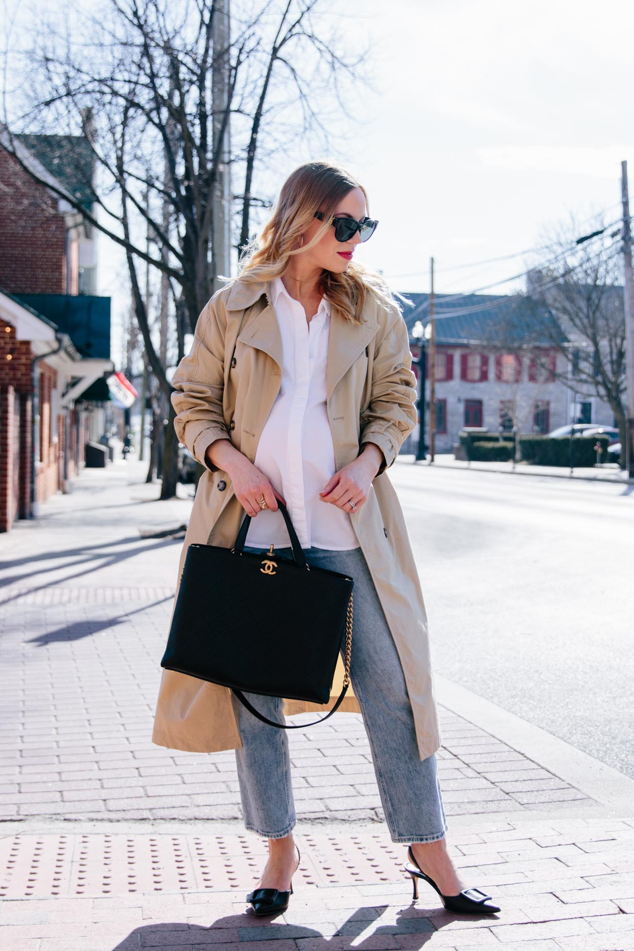 Meagan Brandon fashion blogger of Meagan's Moda wears khaki trench coat with white button shirt, straight leg cropped jeans and Chanel shopping tote spring outfit