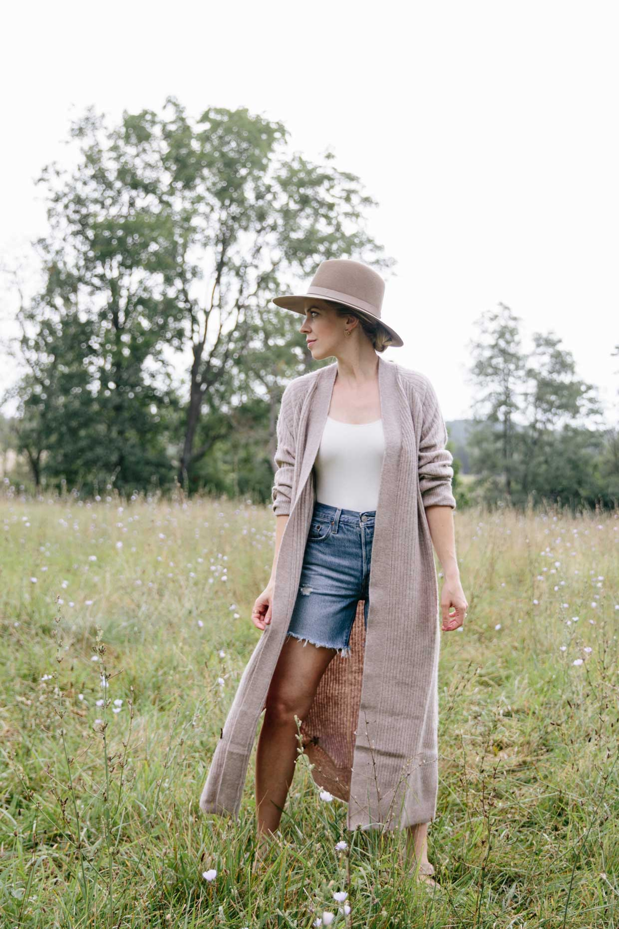 Meagan Brandon style influencer shows how to wear a duster cardigan for early fall with denim shorts and sandals